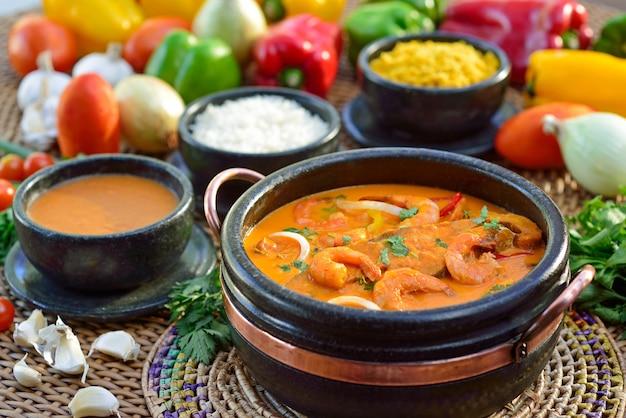 Spezzatino di pesce e gamberi, con riso, polenta e farina di manioca. cibo brasiliano.