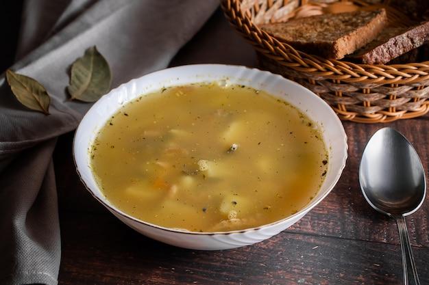 Zuppa di pesce in un piatto su fondo marrone zuppa in un piatto bianco e un cesto con pane ai cereali
