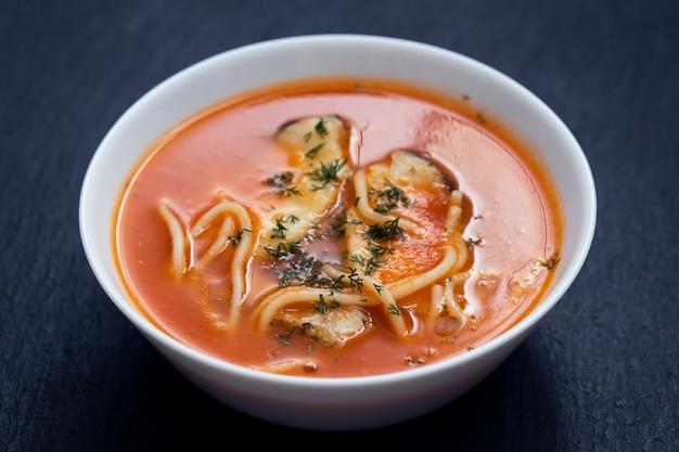 Zuppa di pesce nella ciotola bianca su fondo in ceramica