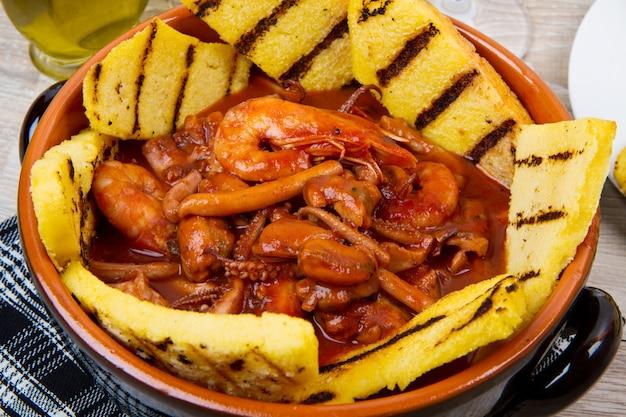 Zuppa di pesce con polenta grigliata su pentola di coccio