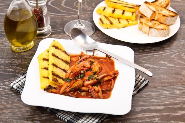 Zuppa di pesce con polenta grigliata su piatto bianco