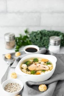 Zuppa di pesce con salmone rosa, cavolfiore e broccoli in una ciotola bianca