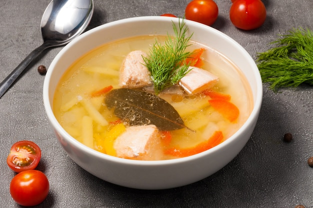 Zuppa di pesce con salmone, patate in una ciotola bianca