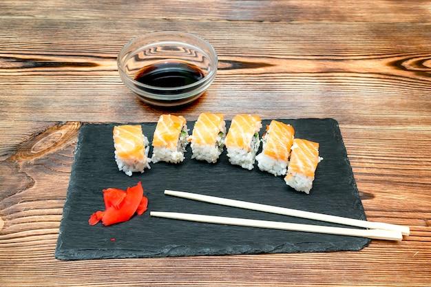 Involtini di sushi di pesce con salmone, zenzero, salsa di soia e bacchette su tagliere nero su sfondo rustico in legno con spazio per copia. frutti di mare, servizio di ristorazione dal concetto di ristorante da vicino.