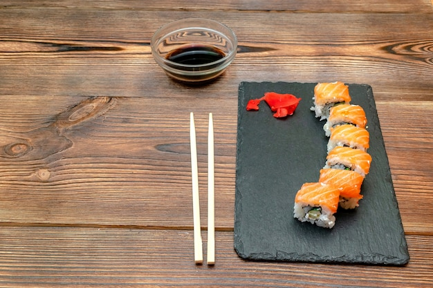 Involtini di sushi di pesce con salmone, zenzero, salsa di soia e bacchette su tavola da portata nera frutti di mare in legno