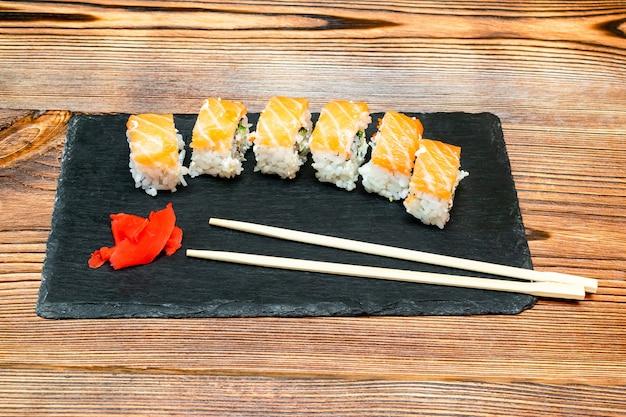 Involtini di sushi di pesce con salmone, wasabi e bacchette su tagliere nero su tavola rustica in legno