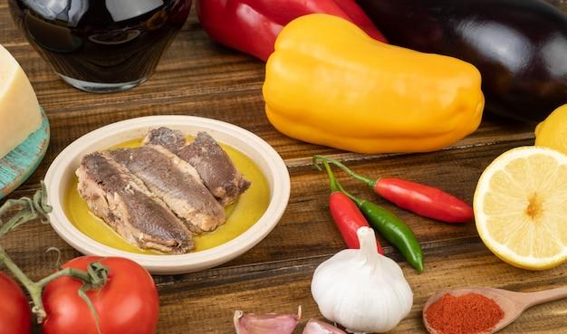 Pesce, pomodori, peperoni, melanzane, olio d'oliva, limone siciliano, vino, pepe e aglio su un tavolo di legno. cibo mediterraneo.