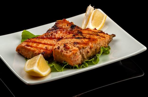 Pesce, trota, salmone, megattera, un pezzo al forno, alla griglia, con una fetta di limone e lattuga