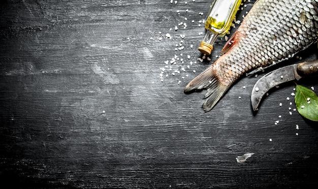 Pesce con un vecchio coltello da intaglio e olio d'oliva. su uno sfondo di legno nero.