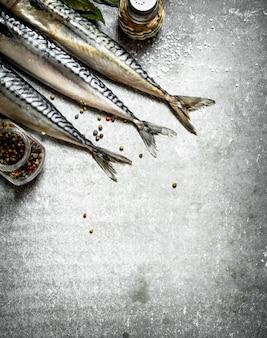 Pesce con pepe in grani e sale sul tavolo di pietra.