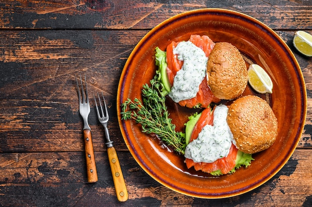 Fishburger con pesce salato, salmone, avocado, panino con hamburger, salsa di senape e insalata iceberg