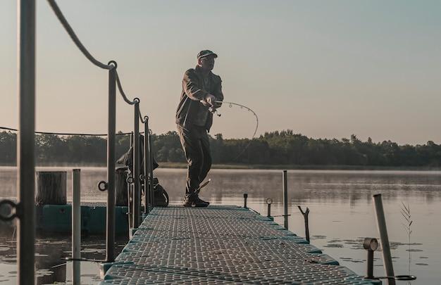 Fisher pesca in mattinata nebbiosa uomo con canna da pesca in appoggio sul lago nella nebbia