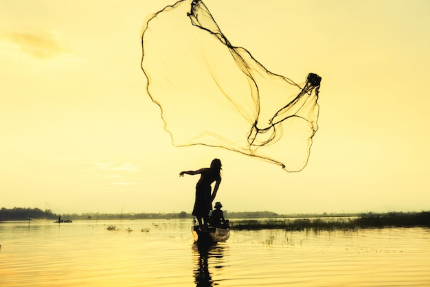 Uomo di fisher che getta pesca della rete da tuffo nel lago con la montagna ed il fondo del cielo blu