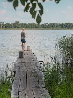 Il pescatore torna sul vecchio molo di legno sull'acqua del lago in estate