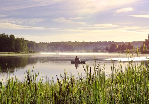 Pescatore su una barca sul lago un gommone sulla superficie dell'acqua tra le canne