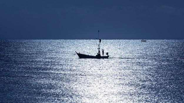 Pescatore sulla sagoma della barca in mare