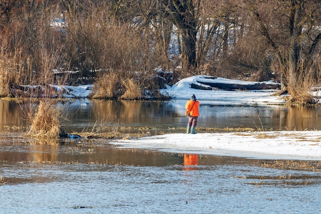 Pescatore in una giacca arancione brillante che cattura pesce su una filatura nel fiume al mattino d'inverno soleggiato.