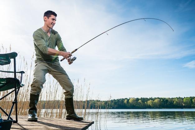 Pescatore che pesca pesce che pesca nel lago