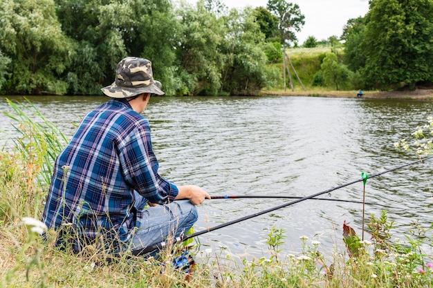 Il pescatore pesca sul lago, pescatore vicino all'acqua con una canna da pesca in una serata tranquilla e calma