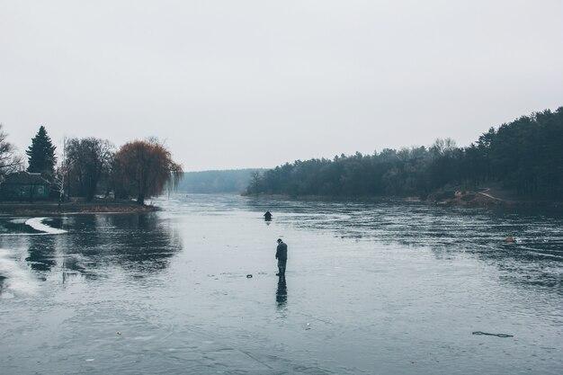 Un pescatore su un fiume ghiacciato sta pescando.
