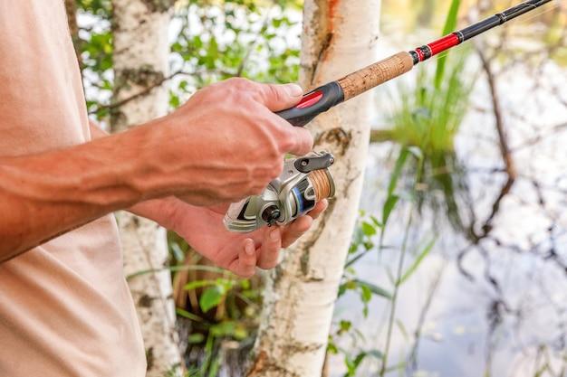 Mani del pescatore con canne da pesca sta pescando in un lago o in un fiume
