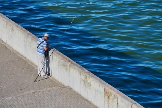 Pescatore che prepara l'esca per la cattura del pesce