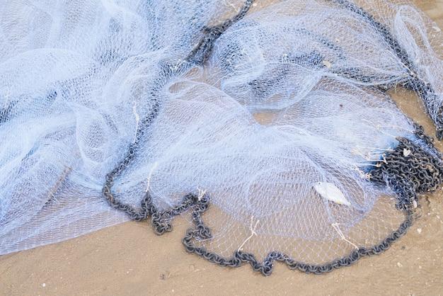 Rete da pesca del pescatore con pesce all'interno sulla spiaggia di sabbia sulla costa del mare