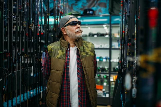Pescatore in occhiali da sole scegliendo l'asta nel negozio di pesca. attrezzature e strumenti per la pesca e la caccia, scelta degli accessori in vetrina in negozio