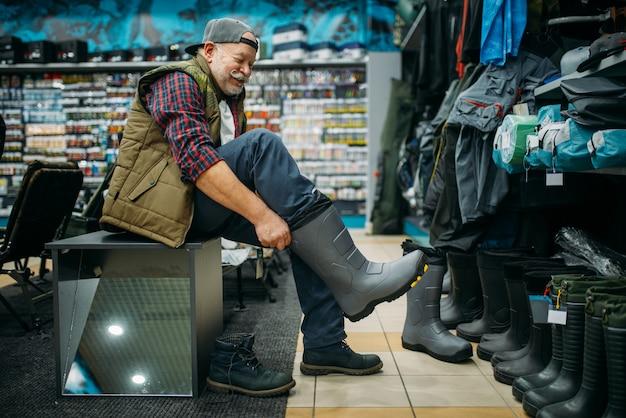 Il pescatore prova gli stivali di gomma nel negozio di pesca. attrezzature e strumenti per la pesca e la caccia, scelta degli accessori in vetrina in negozio