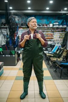 Fisherman prova una tuta di gomma nel negozio di pesca, ganci e palline