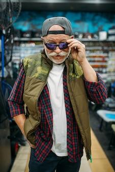Il pescatore prova gli occhiali da sole nel negozio di pesca.