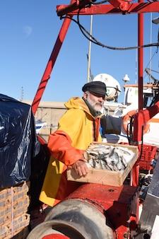 Pescatore con una scatola di pesce all'interno di una barca da pesca