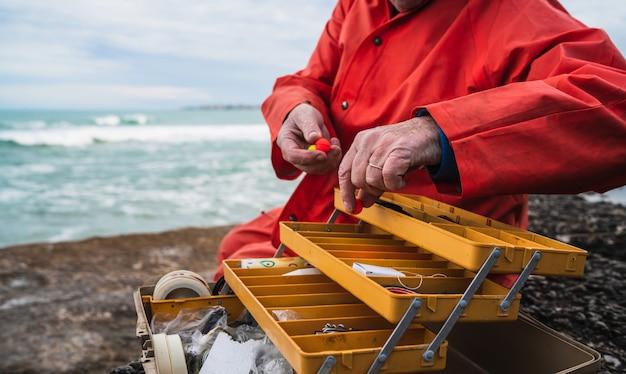 Pescatore con box attrezzatura da pesca.