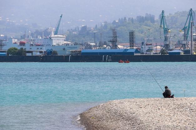 Pescatore con canna da pesca vicino al porto di carico a batumi, georgia