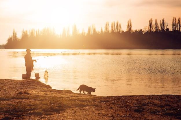 Pescatore con una canna da pesca sulla riva del fiume. gatto. sera.