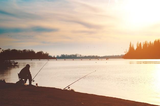 Pescatore con una canna da pesca sulla riva del fiume. sera