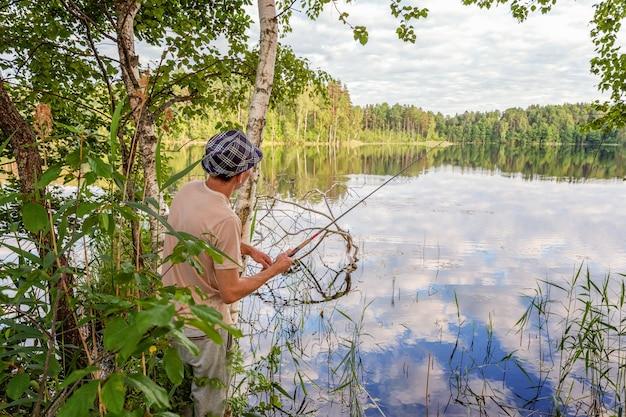 Il pescatore con le canne da pesca sta pescando in un lago o in un fiume