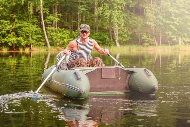 Pescatore con canne da pesca sta pescando in un gommone sul lago o sul fiume