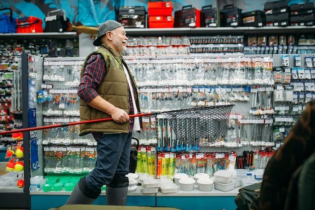 Pescatore con rete e cassetta degli attrezzi nel negozio di pesca, ganci e palline