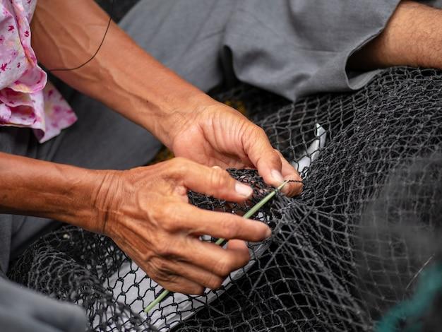 I pescatori stanno riparando le reti da pesca, un pescatore locale al porto che ripara le reti