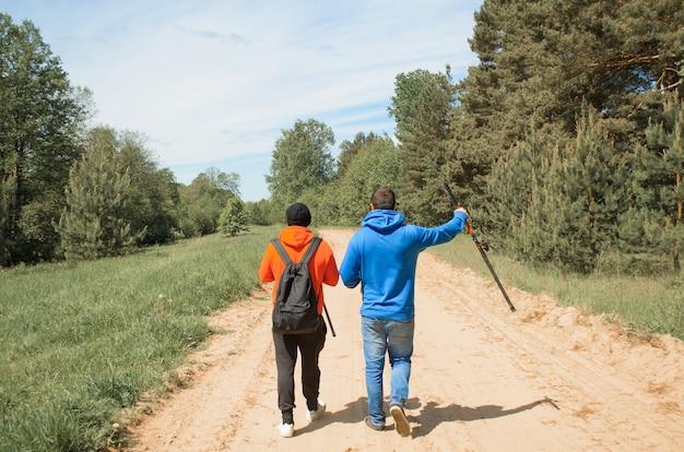Pescatori che vanno a pescare sulla strada, vista posteriore. due persone irriconoscibili con canne da pesca in natura