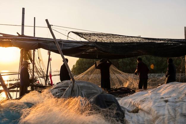 Pescatori che tirano le reti da pesca per prendere il pesce dalla barca al tramonto a samut prakan, thailandia. profili la gente locale al molo del villaggio comunitario via mare. lavoro di squadra in armonia.