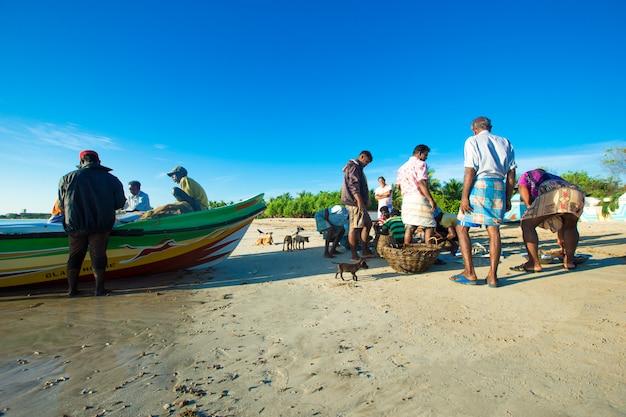 Pescatori con barche di legno in riva al mare