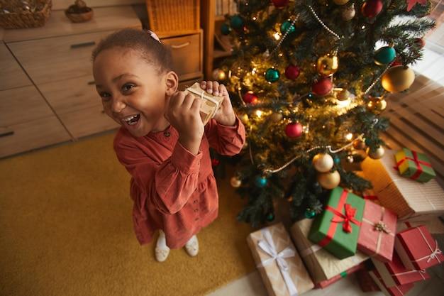 Fisheye ritratto di eccitata ragazza afro-americana che apre i regali di natale in piedi da albero a casa, copia spazio