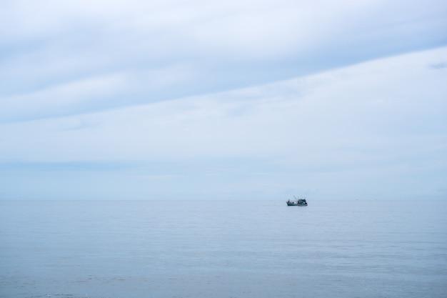 Peschereccio nell'oceano calmo del mare e nel fondo blu chiaro del cielo.