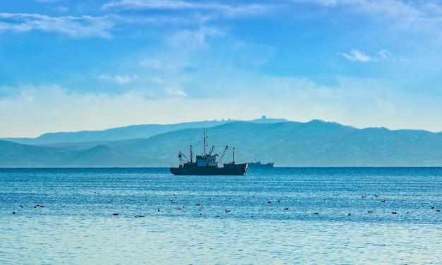 Barca da pesca in mattinata grigia sull'oceano pacifico al largo della penisola di kamchatka