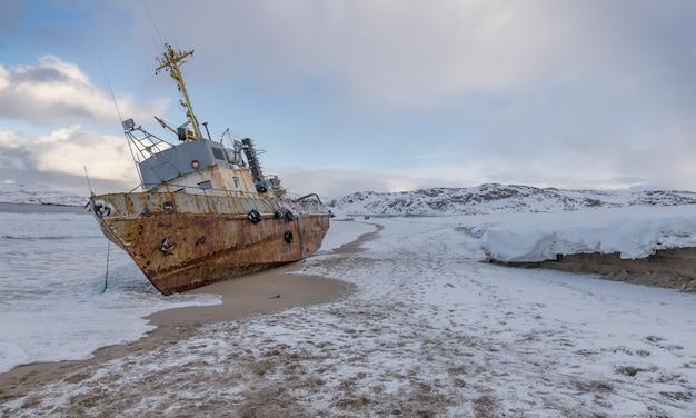 Una barca da pesca sdraiato su un lato, lavato da una tempesta sulla riva del mare di barents, la penisola di kola, teriberka, russia