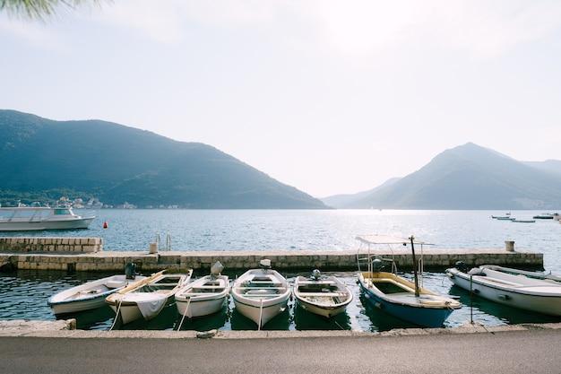 Barche da pesca al molo della città di perast contro le montagne e il cielo blu