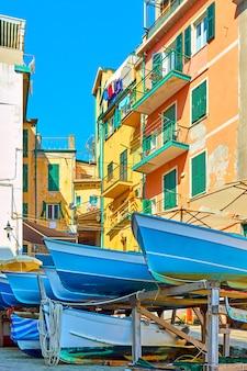 Barche da pesca in strada e vecchie case colorate nella città di riomaggiore nelle cinque terre, la spezia, italy