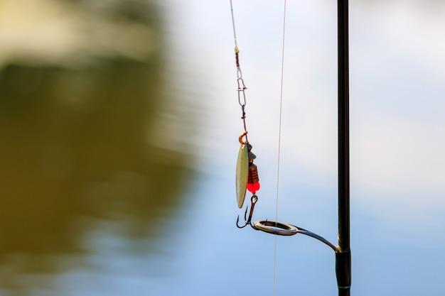 Esca da pesca e canna da spinning close-up contro la superficie dell'acqua